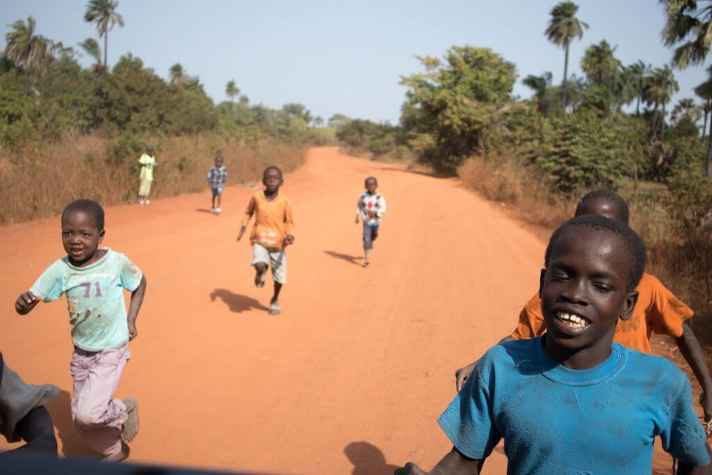 Kinderen rennen achter de auto aan, vragend om geld en snoep