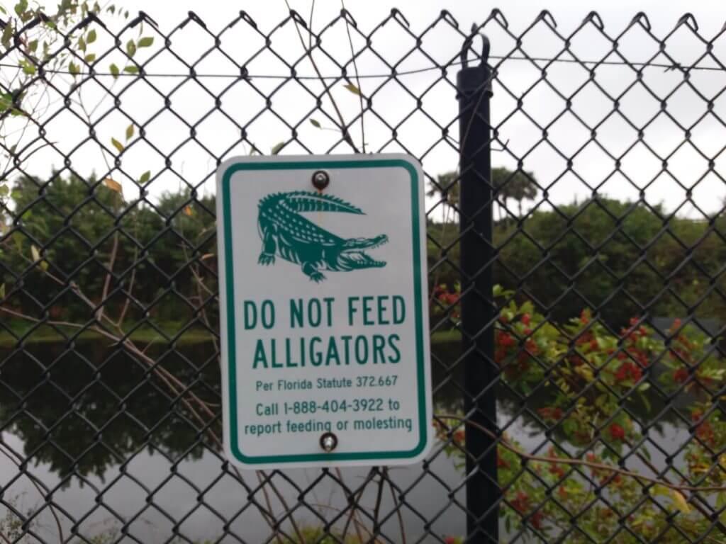 Dit bord aan het hek van het hotel waarschuwt voor alligators